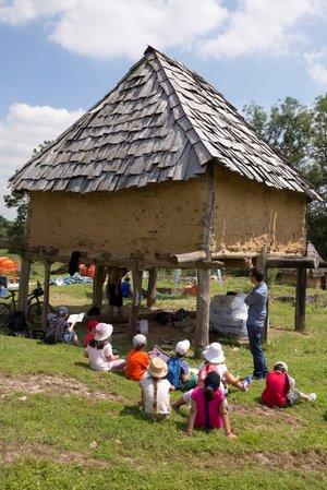 bâtiment en bois surélevé avec des enfants écoutant un guide devant.