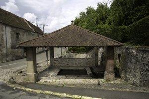 Bassin recouvert d'un toit sur poteaux en pierre au bord d'une rue