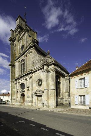 Vue d'une église sur une rue avec son clocher accolé à gauche.